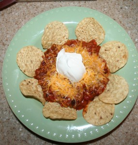 Chili with shredded cheese, sour cream and chips