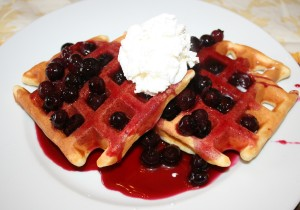 Hot blueberry compote on waffles with whipped cream