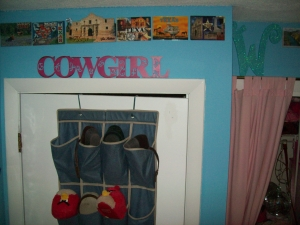 The West Wall is over the back of her door and over her closet. The wall over the door houses her Texas postcards and her Cowgirl sign.