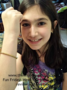 Alex is sporting a gold bracelet made out of guitar strings.