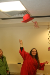Tossing her graduation cap in the private function room at Home & Hospice Care of Rhode Island while her mom looked on.